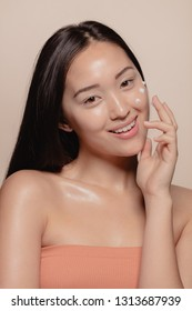 Studio shot of a beautiful young woman applying moisturizer to her face against beige background. Woman looking happy while following skincare regime.