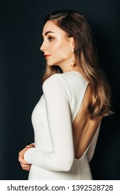 Studio shot of beautiful young woman with long shiny hair, professional makeup, wearing white dress