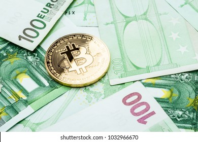 Studio shot of a bitcoin physical golden coin on 100 euro bills banknotes. Bitcoin is a blockchain crypto currency