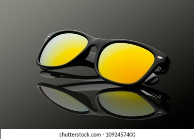 Studio shot of black sunglasses with yellow gradient mirrored. summer is coming concept. Polarizing glasses for safe and pleasant driving car. Yellow/gold polarized lenses.