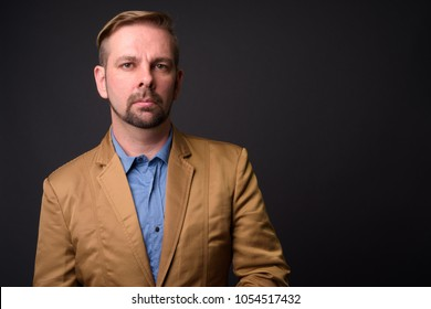 Studio shot of blond bearded businessman with goatee against gray background