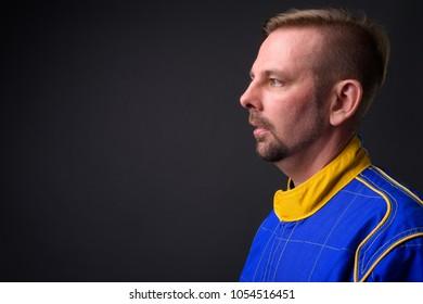 Studio shot of blond bearded man motorcyclist with goatee in full gear against gray background
