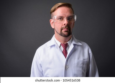 Studio shot of blond bearded man doctor with goatee against gray background