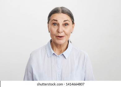 Studio shot of blue eyed gray haired European senior woman in striped blue shirt expressing full disbelief while gossiping with old friend, posing isolated. Age, human emotions and reactions