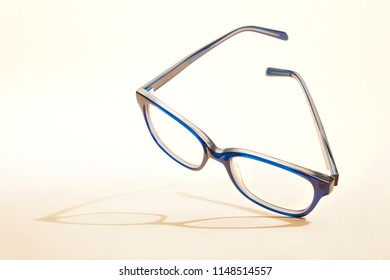 Studio shot of blue glasses with shadow at yellow background.
