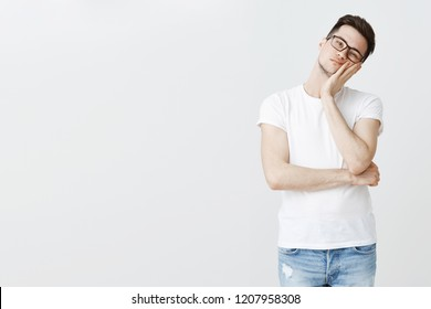 Studio shot of bored indifferent handsome young man leaning face on palm from boredom wasting time watching boring tv show posing on right side of copy space in glasses over gray wall