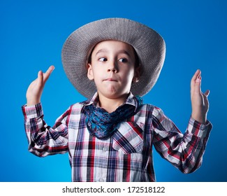 Studio shot of boy dressed up like kowboy pretends  he is surrendering.