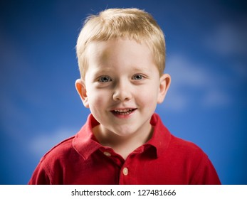 Studio shot of a boy smiling with blue sky and clouds in the background