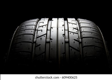 Studio shot of brand new car tire isolated on black background.