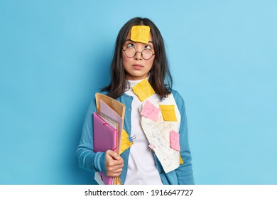 Studio shot of brunette young Asian schoolgirl studies mathematics concentrated above on forehead with sticker holds folders wears round spectacles and sweater isolated over blue background.