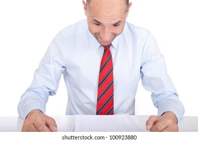 Studio shot of a business man reading a report and being surprised by its content
