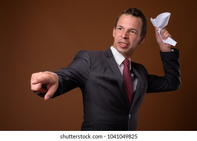Studio shot of businessman wearing suit against brown background