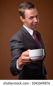Studio shot of businessman wearing suit against brown background