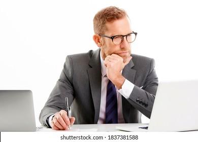 Studioaufnahme eines Geschäftsmanns, der Anzug trägt und beim Arbeiten am Laptop gut aussieht. Einzeln auf weißem Hintergrund.