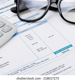 Studio shot of calculator and glasses over some receipt - 1 to 1 ratio