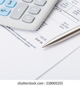 Studio shot of calculator and pen over some receipt - 1 to 1 ratio