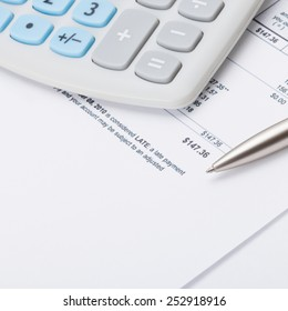 Studio shot of calculator and pen over some receipt under it