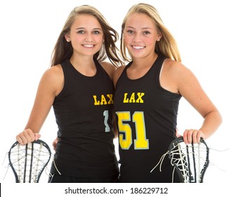 Studio shot, in camera isolation on white background of two beautiful young female lacrosse players with their sticks.
