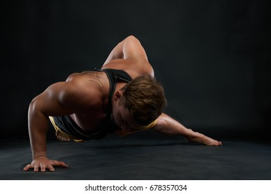Studio shot of Caucasian male athlete with beautiful muscular body doing one-handed push-ups exercise on floor. Sportsman working out in gym. Sports, fitness and active healthy lifestyle concept