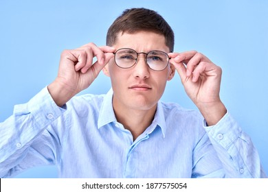 Studio shot caucasian man with poor eyesight holds hands on the rim of glasses and squints, trying to see something, looking at the camera isolated on blue background
