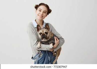Studio shot of caucasian woman and her lovely pet looking on camera with smile. Cheerful female photographer taking picture of herself and pedigree dog lying in her hands. Friendship concept