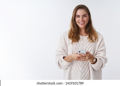Studio shot charming happy smiling woman holding smartphone looking camera positive grinning communicating using app featurused. Female blogger posting pic online smm working via phone
