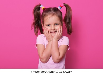 Studio shot of charming small child with two pony tails and many colourful scrunchies, expresses pleasant emotions, touches her cheeks with hands while looking directly at camera, copy spase.