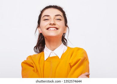 Studio shot of charming young woman, smiles broadly, wears orange sweater with white shirt. Pretty positive student girl feels joyful posing over white studio wall. People and emotions