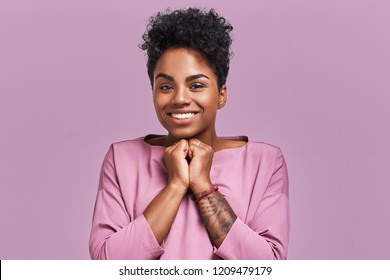 Studio shot of cheerful African American female keeps hands together near chin, smiles broadly, anticipates for surprise prepared by friends on her birthday, isolated over lavender background