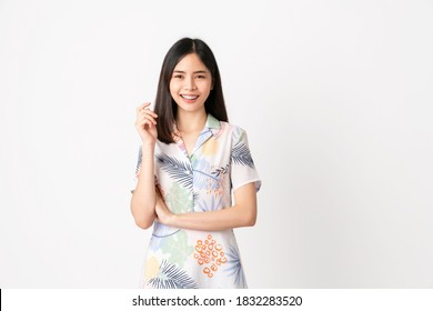 Studio shot of cheerful beautiful Asian woman in light color dress and stand on white background.