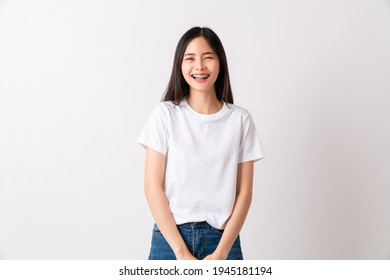 Studio shot of cheerful beautiful Asian woman in white t-shirt and stand smiling with braces on white background.