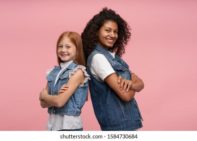 Studio shot of cheerful pretty young girls leaning on each other and smiling happily to camera with broad smiles, keeping hands folded while posing over pink background