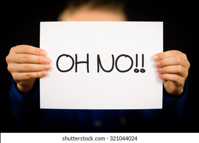 Studio shot of child holding an Oh No sign made of white paper with handwriting.