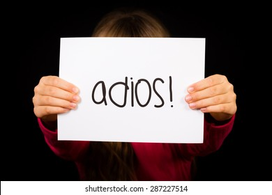 Studio shot of child holding a sign with Spanish word Adios - Goodbye