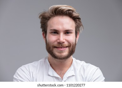 Studio shot close-up portrait of a handsome blond bearded young man smiling happy against beige background for copy space
