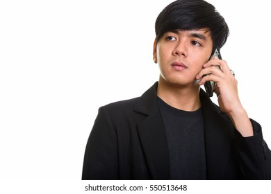 Studio shot of cool handsome Asian man talking on mobile phone while thinking isolated against white background