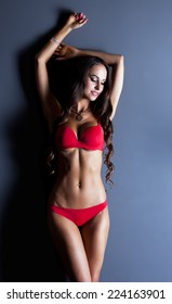 Studio shot of curvy woman in red lingerie