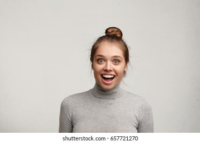 Studio shot of cute astonished fascinated young Caucasian woman with hair bun smiling broadly, feeling excited after her boyfriend made marriage proposal to her unexpectedly and she said Yes