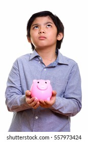 Studio shot of cute Japanese boy holding piggy bank while thinking isolated against white background