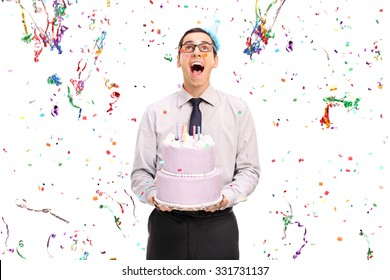 Studio shot of a delighted man holding a birthday cake and looking at the confetti streamers flying around him isolated on white background
