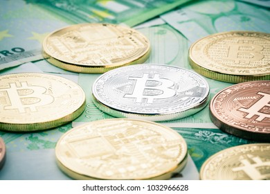 Studio shot of different bitcoin physical golden coins on 100 euro bills banknotes. Bitcoin is a blockchain crypto currency