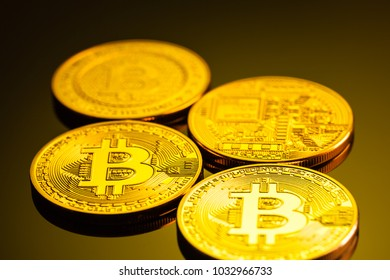 Studio shot of different bitcoin physical golden coins on a dark background. Bitcoin is a blockchain crypto currency