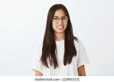 Studio shot of displeased bothered attractive woman in trendy eyewear and white t-shirt, clenching teeth and grimacing from disgust or dislike, being uncomfortable and intense, standing over gray wall