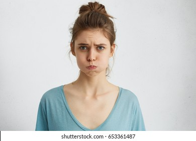 Studio shot of displeased woman with hair knot wearing casual clothes blowing cheeks after quarrel with her boyfriend looking with anger in camera. Human attitudes, emotions and body language concept.