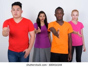 Studio shot of diverse group of multi ethnic friends giving handshake together