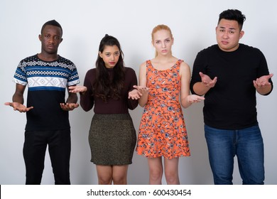 Studio shot of diverse group of multi ethnic friends looking confused together