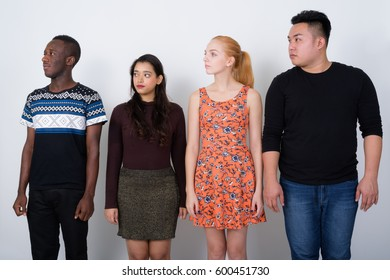 Studio shot of diverse group of multi ethnic friends looking at the left side together