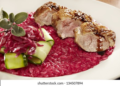 studio shot of duck saute with red beet risotto