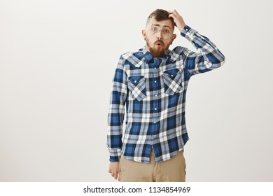 Studio shot of dumb handsome man in plaid shirt and falling glasses, scratching head and folding lips while saying wow, being confused and clueless during math classes, having no idea about topic