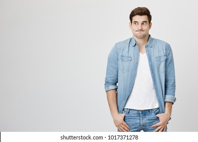 Studio shot of emotional clueless man with trendy haircut in denim shirt over white t-shirt having confused puzzled look, pouting cheeks, shrugging shoulders as he doesn't know reason of accident